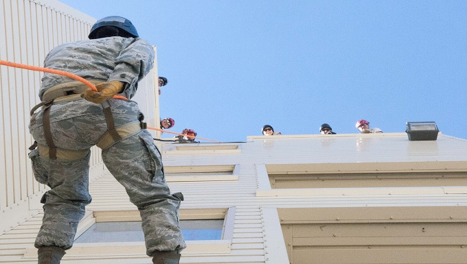 An airman repels down a building while team members look on from above during search and extraction training as part of a Medical Capabilities exercise