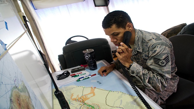 Staff Sergeant Skyler Ross, Air Traffic Control Specialist for the 297th Air Traffic Control Squadron, communicates over a VHF frequency with a civilian helicopter pilot as he checks into the temporary flight restriction airspace in Pahoa